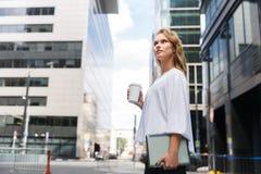 Geschäftsfrau mit Kaffee Takeaway und Tablette auf unscharfem Straßenhintergrund Lizenzfreies Stockbild