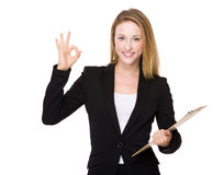 Geschäftsfrau mit Klemmbrett und okayzeichen Lizenzfreie Stockbilder