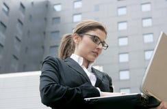 Geschäftsfrau mit Laptop-Computer auf der Stadt lizenzfreie stockfotos