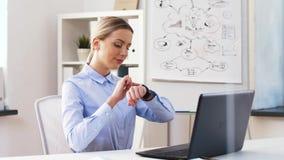 Geschäftsfrau mit Laptop und smartwatch im Büro stock footage