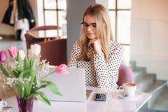 Geschäftsfrau mit Laptop und Telefon im Café Glückliches Arbeiten des jungen Mädchens stockfotografie