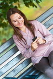 Geschäftsfrau mit Mobiltelefon und Laptop auf der Bank im Park Stockfoto