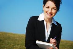 Geschäftsfrau mit Notizblock Stockbild