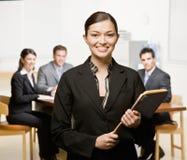 Geschäftsfrau mit Notizbuch und Mitarbeitern Stockfotos