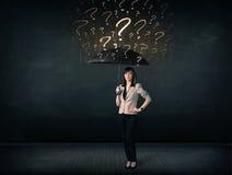 Geschäftsfrau mit Regenschirm und vielen gezogenen Fragezeichen Stockfoto