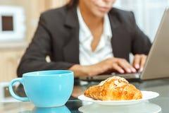 Geschäftsfrau mit Schale von coffe und von Hörnchen Stockfoto