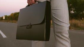 Geschäftsfrau mit schwarzem Aktenkoffer in ihrer Hand, steigt in Hose und in Jacke auf dem Asphalt, Abschluss stock video
