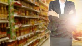 Geschäftsfrau mit Supermarkthintergrund für Investition ungefähr stockfotos