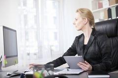 Geschäftsfrau mit Tablet unter Verwendung eines Tischrechners Lizenzfreies Stockbild
