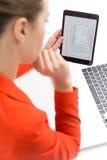 Geschäftsfrau mit Tablette und Laptop denkend über Idee Stockbild
