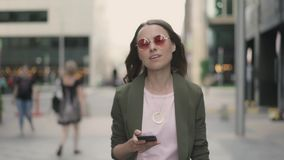 Geschäftsfrau mit Telefon gehend in unscharfe Stadtstraße und -c$lächeln stock footage