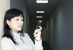 Geschäftsfrau mit Telefon im Flur Stockfoto