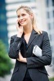 Geschäftsfrau mit Telefon und Zeitungen Stockbild
