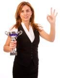 Geschäftsfrau mit Trophäe machen okaygeste Lizenzfreie Stockfotografie