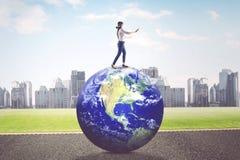 Geschäftsfrau mit verbundenen Augen geht auf Erdplaneten Stockfotos