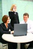 Geschäftsfrau mit zwei Teilnehmern auf Computer Lizenzfreie Stockbilder