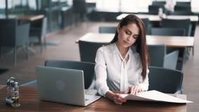 Geschäftsfrau am Mittag in den Caféblicken auf Menü, Laptop auf Tabelle, Zeitlupe stock video