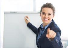 Geschäftsfrau nahe flipchart in camera zeigend Lizenzfreies Stockfoto