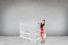 Geschäftsfrau nahe großem Eiswürfel Stockbild