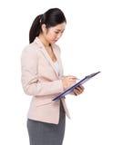 Geschäftsfrau nehmen Kenntnis über Klemmbrett Lizenzfreie Stockfotografie