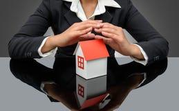 Geschäftsfrau- oder Immobilienmakler und Halten eines Musterhauses Lizenzfreie Stockfotos