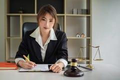 Geschäftsfrau oder Rechtsanwälte, die Vertragspapiere mit Messingskala auf hölzernem Schreibtisch im Büro besprechen Gesetz, Rech stockfotografie