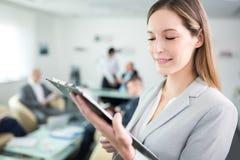 Geschäftsfrau-Reading Document On-Klemmbrett im Büro lizenzfreies stockfoto