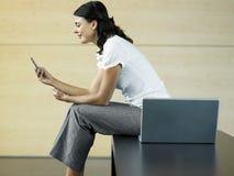Geschäftsfrau Reading Text Message in der Lobby Lizenzfreies Stockbild