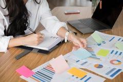 Geschäftsfrau schreiben Anmerkung auf Notizbuch am Arbeitsplatz Startfrau stockfoto