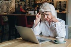 Geschäftsfrau sitzt bei Tisch vor Laptop und Blicken nah am Monitor und hebt ihre Gläser an Ausbildung für Erwachsene Lizenzfreies Stockbild