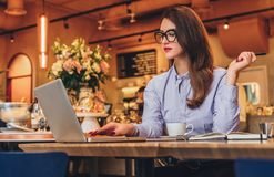 Geschäftsfrau sitzt im Café bei Tisch und arbeitet auf Laptop Hippie-Mädchen, das, Graseninternet, E-Mail überprüfend blogging is Stockfotografie
