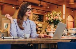 Geschäftsfrau sitzt im Café bei Tisch und arbeitet auf Laptop Hippie-Mädchen, das, Graseninternet, E-Mail überprüfend blogging is Stockbilder