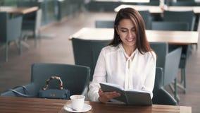 Geschäftsfrau sitzt im Café, trinkt Kaffee und betrachtet ihr Tagebuch, Zeitlupe stock footage