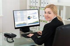 Geschäftsfrau Smiling While Working auf Computer Stockbilder