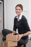 Geschäftsfrau sortiert Pakete Stockfotografie