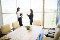 Geschäftsfrau sprechen mit ihrem Sekretär in ihrem Büroraum stockfotografie