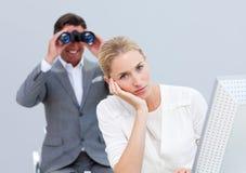Geschäftsfrau störte durch einen Mann, der Binokel verwendet Stockfotos