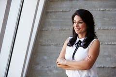 Geschäftsfrau Standing Against Wall im modernen Büro Stockbilder