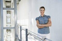 Geschäftsfrau Standing Arms Crossed im Büro-Korridor Stockfotos