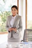 Geschäftsfrau Standing In Boardroom mit Digital-Tablet Stockfoto