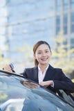 Geschäftsfrau Standing durch das Auto, Kamera betrachtend Stockbild