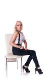 Geschäftsfrau steht nahe einem Stuhl stockfotografie