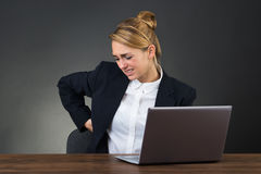 Geschäftsfrau Suffering From Backpain bei der Anwendung des Laptops lizenzfreie stockfotos