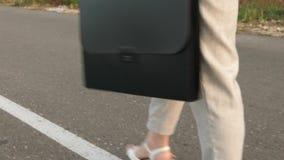 Geschäftsfrau trägt schwarzen Aktenkoffer mit Dokumenten in ihrer linken Hand Weiblicher Rechtsanwalt geht auf Weise zum Geschäft stock video footage