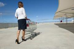 Geschäftsfrau und Einkaufenlaufkatze Lizenzfreie Stockfotografie