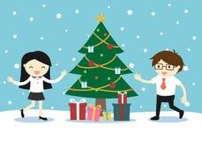 Geschäftsfrau und Geschäftsmann, die mit einem Weihnachtsbaum und Geschenkboxen glücklich sich fühlt Lizenzfreies Stockbild