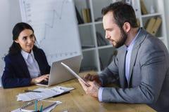 Geschäftsfrau und Geschäftsmann, die mit Laptop und Tablette arbeiten lizenzfreie stockfotografie