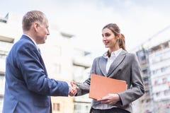 Geschäftsfrau und Geschäftsmann machen ein Abkommen im Freien Stockbild