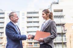 Geschäftsfrau und Geschäftsmann machen ein Abkommen im Freien Lizenzfreie Stockbilder
