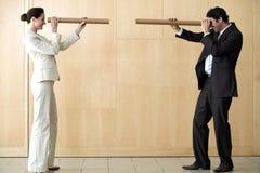 Geschäftsfrau und Mann, die durch Gefäße blicken Stockfoto